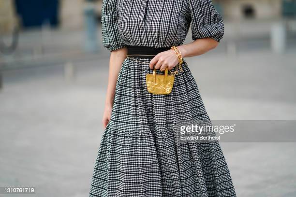 Maria Rosaria Rizzo @lacoquetteitalienne wears a grey gathered checked dress with puff sleeves from Parosh, a golden bracelet, a golden mini bag from...