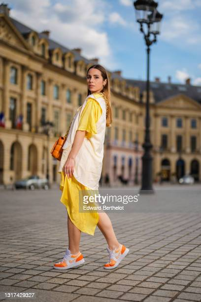 Maria Rosaria Rizzo @lacoquetteitalienne wears a pale pastel yellow and beige shirt / flowing dress from Victoria/Tomas, a brown leather Bottega...