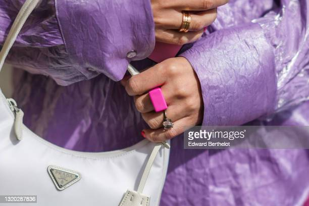 Maria Rosaria Rizzo @lacoquetteitalienne wears a pale purple belted oversized MSGM silk shirt, a white Prada Re-edition 2000 handbag, a silver heart...