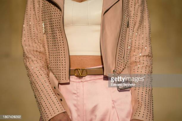 Maria Rosaria Rizzo @lacoquetteitalienne wears a pink studded leather jacket, a white low-neck crop top, a Valentino belt, pink flare silky pants, on...