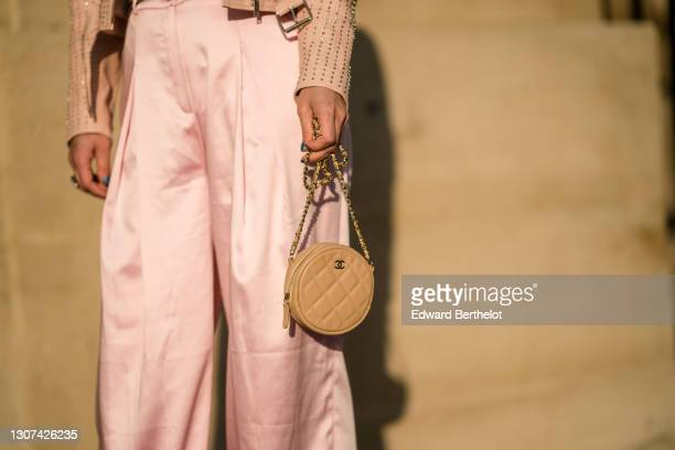 Maria Rosaria Rizzo @lacoquetteitalienne wears a pink studded leather jacket, a Chanel round quilted bag, pink flare silky pants, on March 05, 2021...