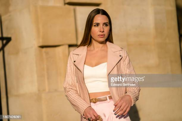 Maria Rosaria Rizzo @lacoquetteitalienne wears a pink studded leather jacket, a white low-neck crop top, a Valentino belt, on March 05, 2021 in...
