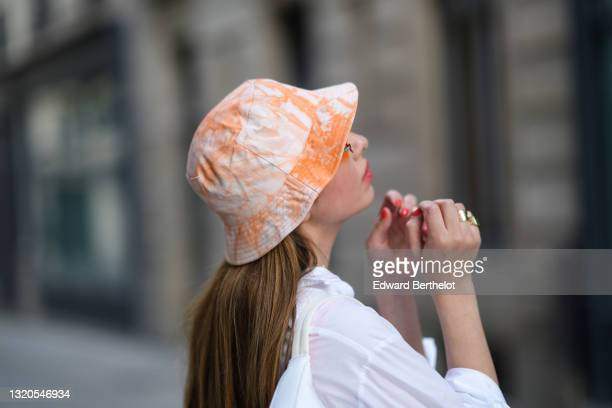 Maria Rosaria Rizzo @lacoquetteitalienne wears a white and orange tie and dye bob hat, orange sunglasses, a white oversized shirt, gold rings, on May...