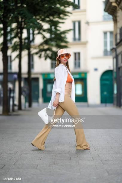 Maria Rosaria Rizzo @lacoquetteitalienne wears a white and orange tie and dye bob hat, orange sunglasses, a gold chain pendant earring, a white...