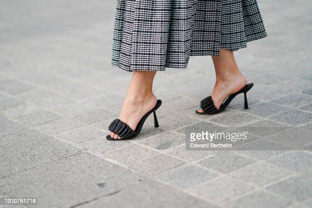 Maria Rosaria Rizzo @lacoquetteitalienne wears black leather sandals shoes from LPA, on March 03, 2021 in Paris, France.