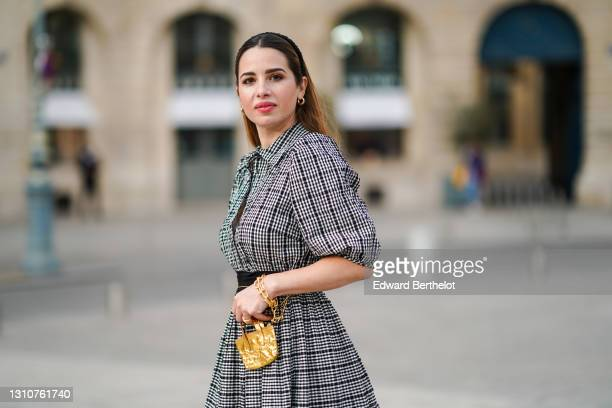 Maria Rosaria Rizzo @lacoquetteitalienne wears earrings, a grey gathered checked dress with puff sleeves from Parosh, a golden bracelet, a golden...
