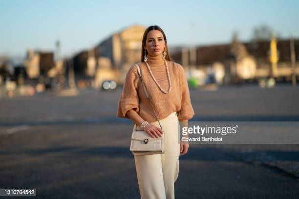 Maria Rosaria Rizzo @lacoquetteitalienne wears earrings, a pearl necklace, a wool turtleneck oversized pullover with puff sleeves from Ann...