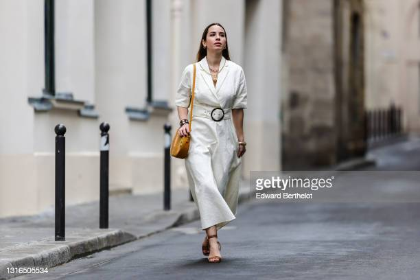Maria Rosaria Rizzo @lacoquetteitalienne wears gold earrings, a gold chain necklace, a gold chain pendant necklace, a white blazer collar rolled-up...