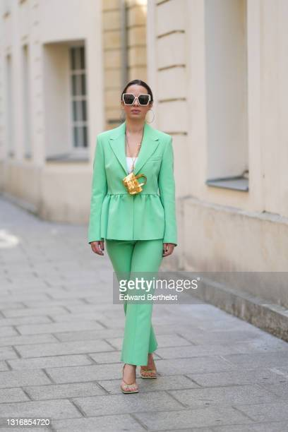 Maria Rosaria Rizzo @lacoquetteitalienne wears large circular earrings, sunglasses, a white top, a pale pastel green gathered blazer jacket, with...