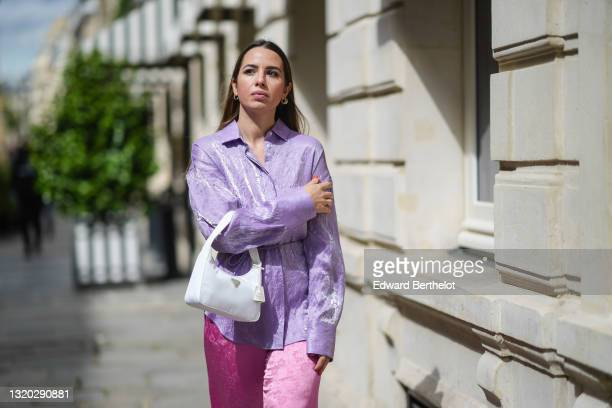 Maria Rosaria Rizzo @lacoquetteitalienne wears silver earrings, a pale purple belted oversized MSGM silk shirt, pink flower pattern silk MSGM flared...
