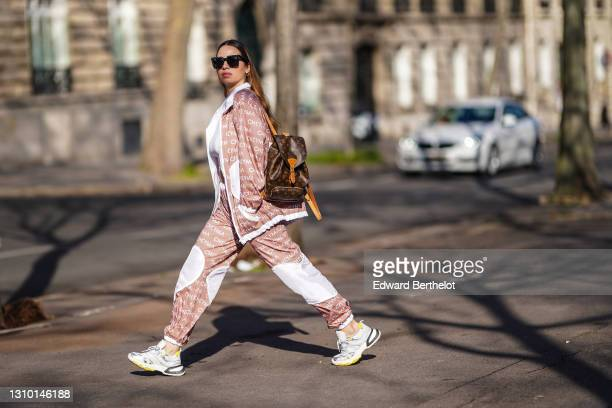 Maria Rosaria Rizzo @lacoquetteitalienne wears sunglasses from Celine, a golden chain necklace, a white cropped top, a total Cheyma sportswear look...