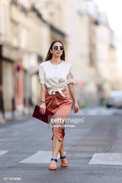 Maria Rosaria Rizzo @lacoquetteitalienne wears white Dior sunglasses, gold earrings, a gold chain necklace, a white Natan t-shirt tied in front with...