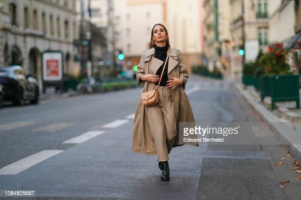 Maria Rosaria Rizzo wears a beige trench coat from Zeynep Arcay, a Saint Laurent YSL beige bag, a black turtleneck wool pullover, pale brown leather...