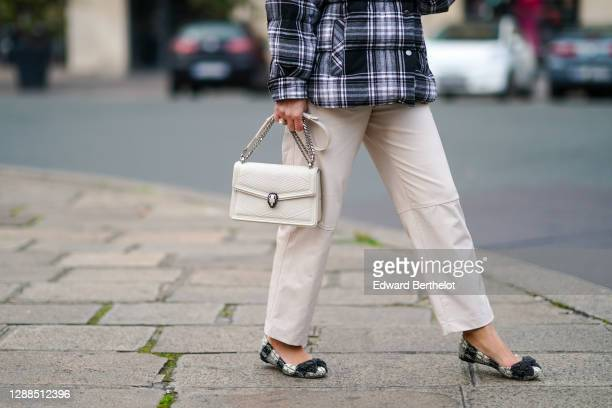 Maria Rosaria Rizzo wears a black and white checked pattern puffer winter Parosh coat, white Twinset pants, a Bulgari bag, flat shoes from Tory...