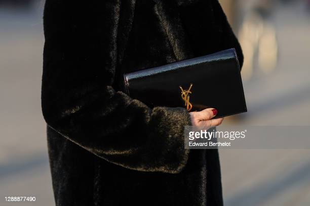 Maria Rosaria Rizzo wears a black faux fur fluffy long coat from Lovers + Friends, a Saint Laurent YSL black leather clutch/bag, on November 30, 2020...