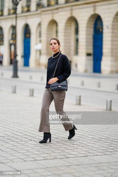 Maria Rosaria Rizzo wears a black turtleneck pullover from Natan Couture, a Chanel black leather quilted bag, beige flared pants from Parosh, Zara...