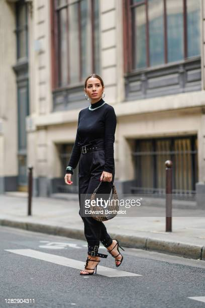 Maria Rosaria Rizzo wears a black turtleneck pullover with a bejeweled strass part from NBD, golden earrings, a leopard print Fendi bag, a belt,...