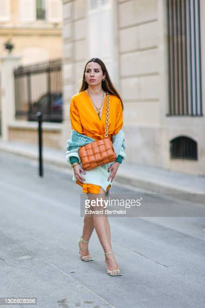 Maria Rosaria Rizzo wears a Chanel long golden necklace, an orange low-neck v-neck dress from Verguenza, a brown quilted woven leather Bottega Veneta...