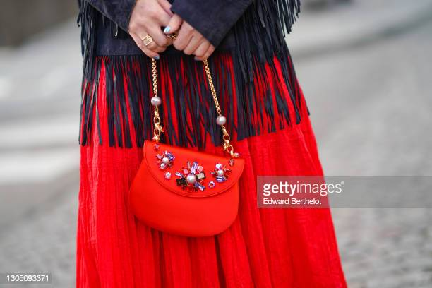 Maria Rosaria Rizzo wears a red dress from Parosh, a dark navy blue jacket with long fringes and pockets from Parosh, a red bejeweled bag from...