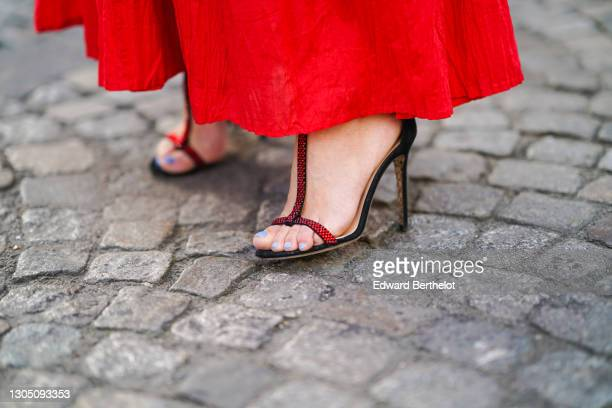 Maria Rosaria Rizzo wears a red dress from Parosh, high heels shoes from Paciotti, on March 02, 2021 in Paris, France.