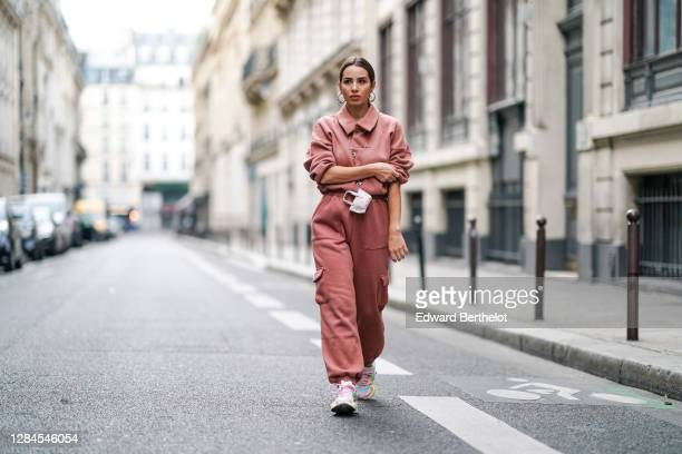 Maria Rosaria Rizzo wears a salmon pink sportswear outfit from Tularosa made of a sweater and pants with cargo pockets, Puma pastel colored sneakers...
