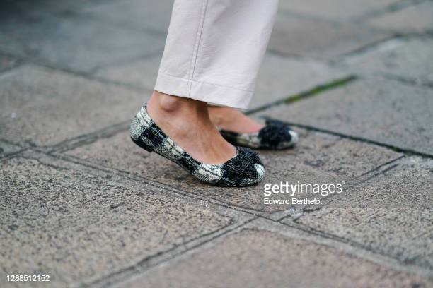 Maria Rosaria Rizzo wears black and white checked flat shoes from Tory Burch, on November 29, 2020 in Paris, France.