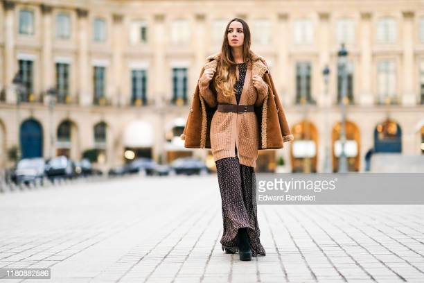 Maria Rosaria Rizzo wears brown wool jacket, a large belt, a dress with a printed geometric patterns, a brown aviator jacket with sheep wool inner...