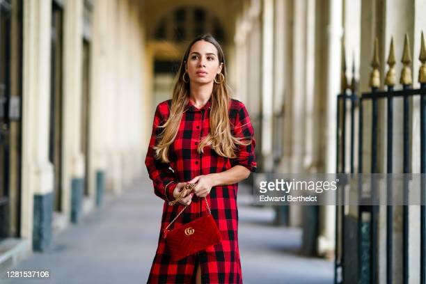 Maria Rosaria Rizzo wears earrings a black and red checkered shirt / long dress with fringes a red velvet padded Gucci bag on October 21 2020 in...