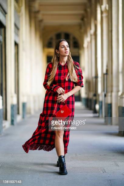 Maria Rosaria Rizzo wears earrings a black and red checkered shirt / long dress with fringes a red velvet padded Gucci bag black leather Vuitton...