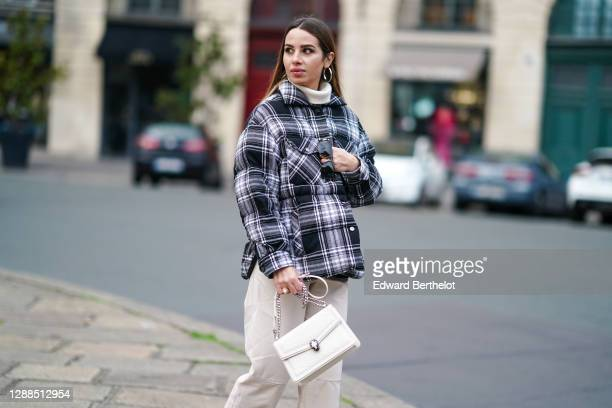 Maria Rosaria Rizzo wears earrings, a black and white checked pattern puffer winter Parosh coat, a white wool turtleneck pullover, white Twinset...