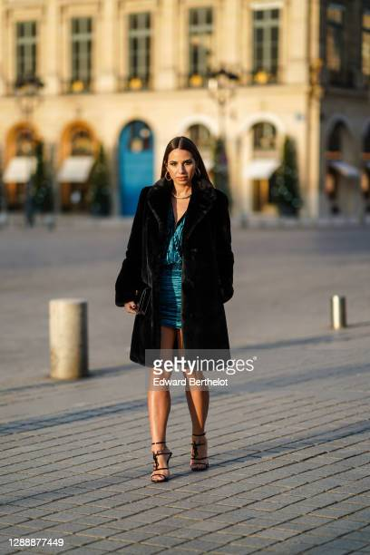 Maria Rosaria Rizzo wears earrings, a golden necklace from Raspini, a black faux fur fluffy long coat from Lovers + Friends, a blue / turquoise short...