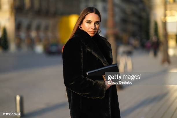 Maria Rosaria Rizzo wears earrings, a golden necklace from Raspini, a black faux fur fluffy long coat from Lovers + Friends, a Saint Laurent YSL...