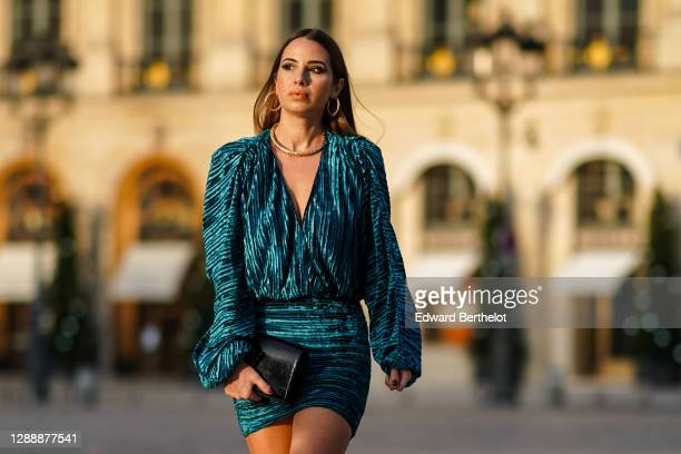 Maria Rosaria Rizzo wears earrings, a golden necklace from Raspini, a blue / turquoise short pleated shiny dress from NBD, a Saint Laurent YSL black...