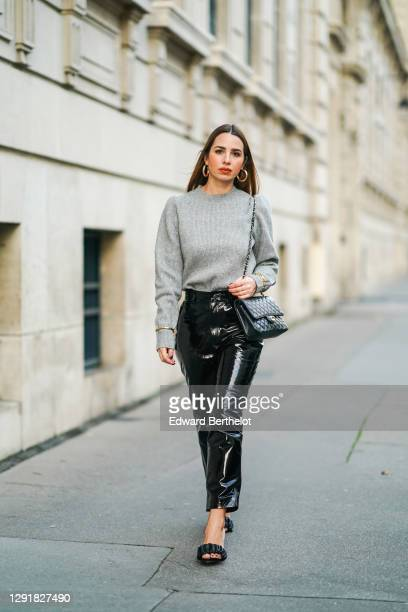 Maria Rosaria Rizzo wears golden earrings, a gray wool pullover from Tularosa, a black quilted Chanel bag, golden bracelets and jewelry, black shiny...