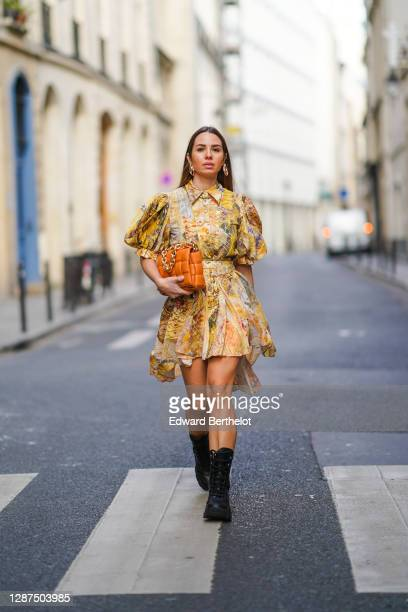 Maria Rosaria Rizzo wears golden earrings, a yellow short flowing ruffled dress / shirt with puff sleeves and floral print from Leo&Lin, an...