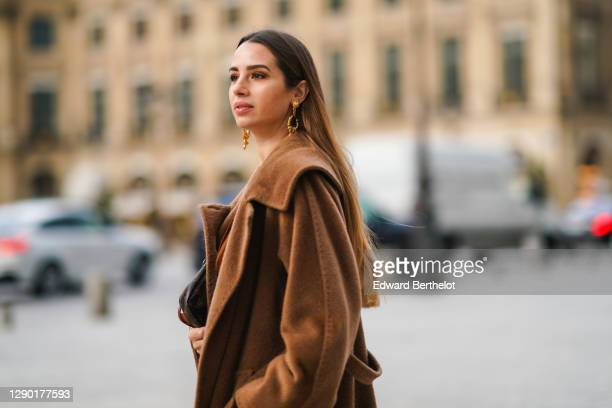 Maria Rosaria Rizzo wears golden long earrings from Raspini, a brown fluffy long winter coat from Max Mara, on December 04, 2020 in Paris, France.
