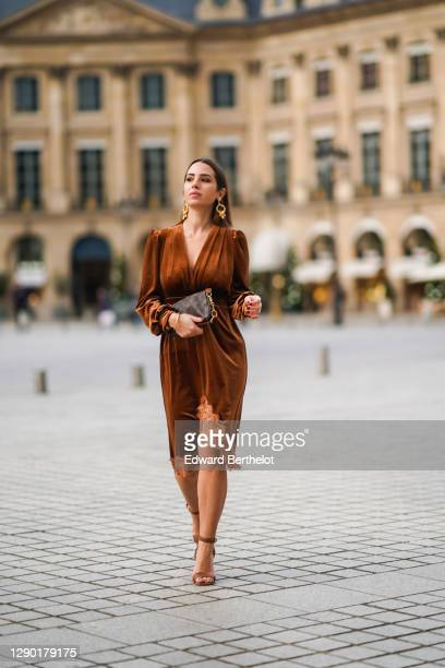Maria Rosaria Rizzo wears golden long earrings from Raspini, a brown velvet low-neck v-neck dress with lace and floral embroidery on the bottom part...