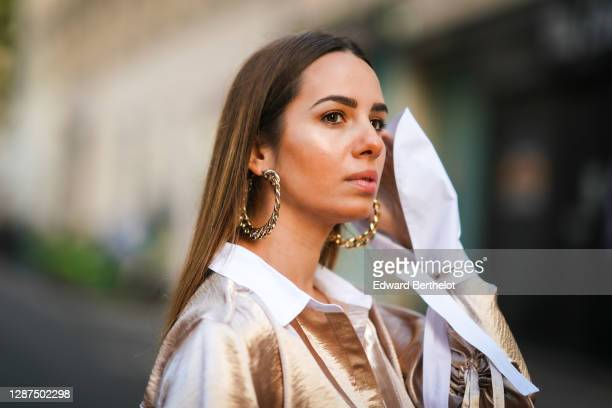"""Maria Rosaria Rizzo wears large golden earrings from """"Alcoolique"""", a satin / silky shiny bronze colored lustrous flowing shirt from Andrea Szántó, on..."""