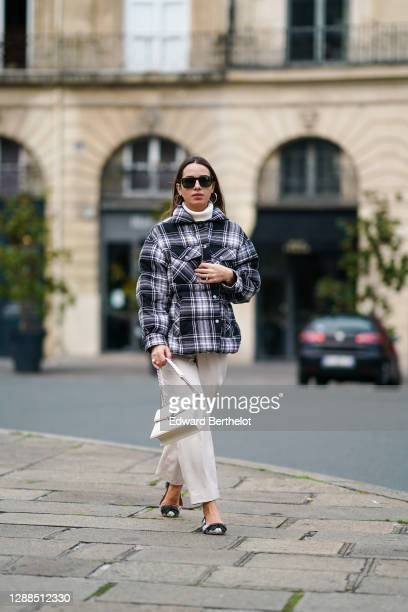 Maria Rosaria Rizzo wears Persol sunglasses, earrings, a black and white checked pattern puffer winter Parosh coat, a white wool turtleneck pullover,...