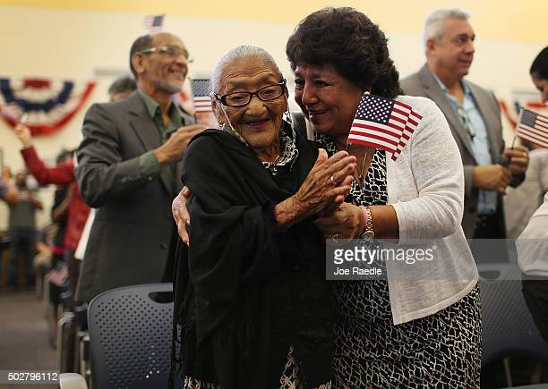 Maria Rosario Corrales hugs her mother Juana Hernandez who is 101 years old and originally from Honduras after she had been sworn in as a naturalized...