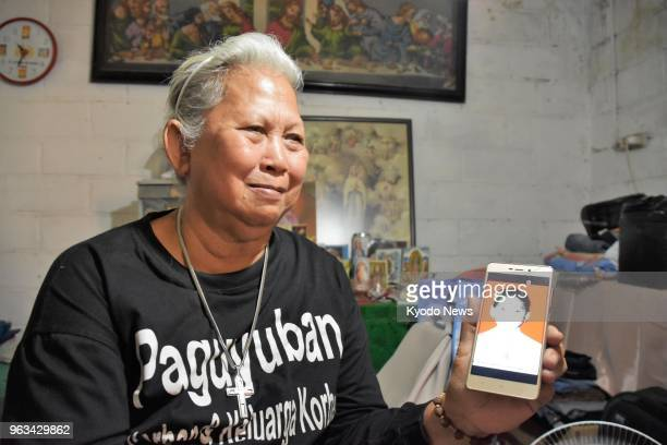 Maria Sanu in this photo taken on May 10 2018 at her home in East Jakarta shows a photo of her 15yearold son Stefanus who went missing in May 1998 in...