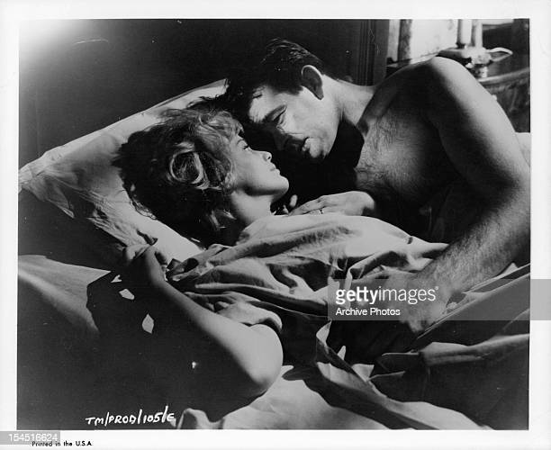 Maria Schell lies in bed with Stuart Whitman in a scene from the film 'The Mark' 1961