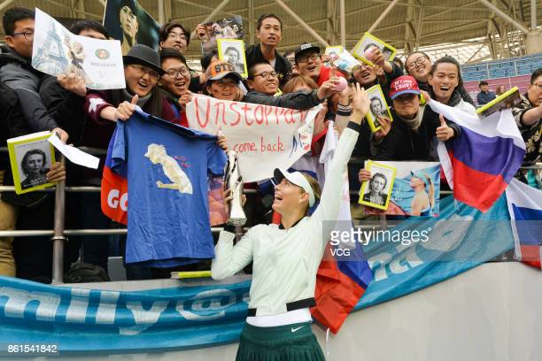 Maria Sharapova of Russia celebrates with her trophy after winning the women's singles final match against Aryna Sabalenka of Belarus at the WTA...