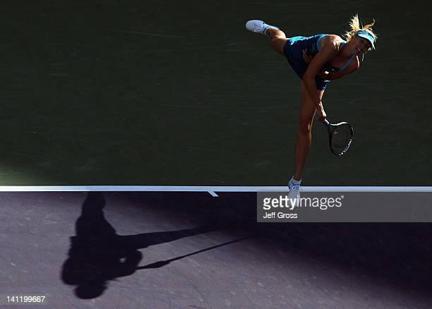 Maria Sharapova of Russia follows through on a serve to Simona Halep of Romania during the BNP Paribas Open at the Indian Wells Tennis Garden on...