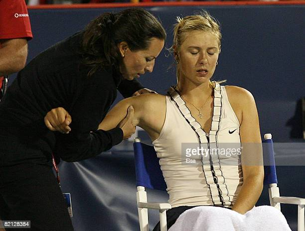 Maria Sharapova of Russia has her shoulder worked on in the second set against Marta Domachowska of Poland during Day 3 of Rogers Cup Tennis on July...