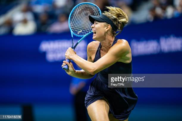 Maria Sharapova of Russia hits a backhand against Serena Williams of the United States in the first round of the US Open in Arthur Ashe Stadium at...