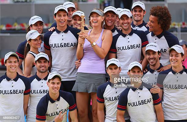 Maria Sharapova of Russia holds her winners trophy whilst she poses for a photograph with the ball boys after her three set victory against Simona...