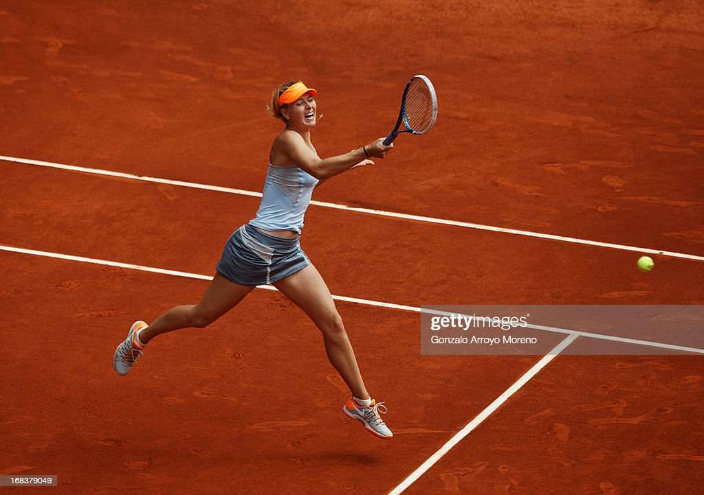 Maria Sharapova of Russia jumps to play a forehand to Sabine Lisicki of Germany on day six of the Mutua Madrid Open tennis tournament at the Caja Magica on May 9, 2013 in Madrid, Spain.