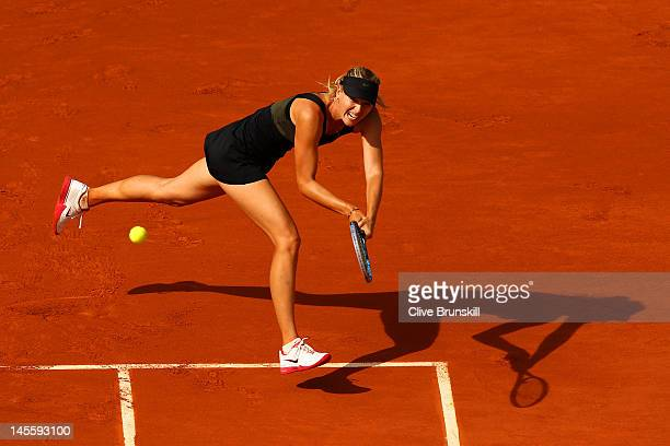 Maria Sharapova of Russia plays a backhand in her women's singles third round match against Shuai Peng of China during day 7 of the French Open at...