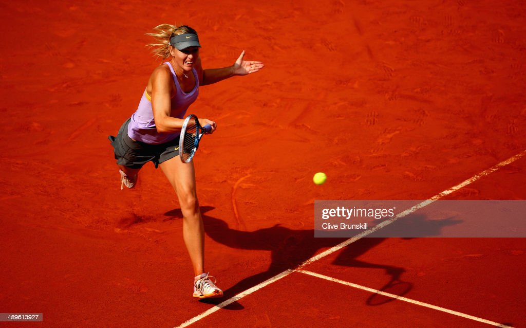 Maria Sharapova of Russia plays a forehand against Simona Halep of Romania in their final match during day nine of the Mutua Madrid Open tennis tournament at the Caja Magica on May 11, 2014 in Madrid, Spain.
